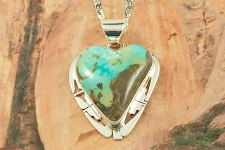 Genuine Candelaria Boulder Turquoise set in Sterling Silver Pendant. The cabochon is Candelaria Boulder Turquoise, you can see the veins of Turquoise running through the host rock.  The Candelaria mine is located in Esmeralda County, Nevada. Created by Navajo Artist Phillip Sanchez. Signed by the artist. Free 18 inch Sterling Silver Chain with purchase of pendant.